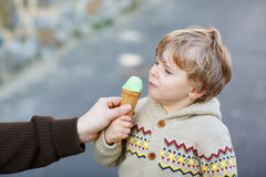 Gelukkig weinig jongen die roomijs eten, in openlucht Stock Foto's