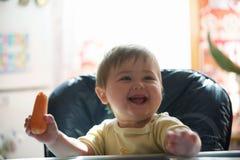 Gelukkig weinig jongen die wortelen houden Concept gezond voedsel royalty-vrije stock fotografie