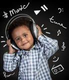Gelukkig weinig jongen het luisteren muziek stock fotografie
