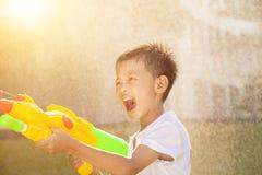 Gelukkig weinig jongen het schreeuwen en het spelen waterkanonnen in het park Stock Foto's