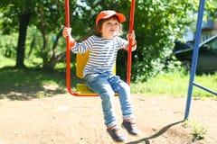 Gelukkig weinig jongen (2 11 jaar die) op playpit slingeren Stock Foto