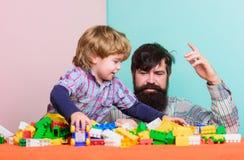 gelukkig weinig jongen met gebaarde mensenpapa die samen spelen vader en zoonsspelspel de bouwhuis met kleurrijk stock foto
