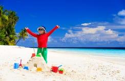 Gelukkig weinig jongen met gebouwd zandkasteel op strand Stock Afbeeldingen