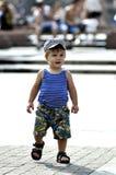 Gelukkig weinig jongen in vest en borrelsgangen op straat royalty-vrije stock afbeeldingen