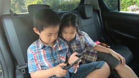 Gelukkig weinig jongensmeisje die smartphone van de veiligheidsgordelsgreep in auto dragen stock videobeelden