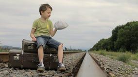 Gelukkig weinig jongenszitting op de spoorweg stock footage