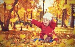 Gelukkig weinig kind, babymeisje die en in de herfst lachen spelen Stock Foto