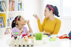 Gelukkig weinig kind en haar moedergreep geschilderde eieren stock fotografie