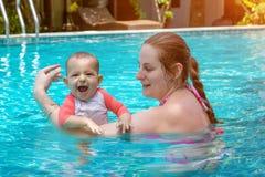 Gelukkig weinig kind met moeder, Baby eerste keer in een groot pool en zeer ge?mponeerd Zeer gelukkige de zuigeling en stoeit royalty-vrije stock afbeelding