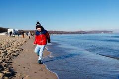 Gelukkig weinig kindjongen die op het strand lopen royalty-vrije stock foto