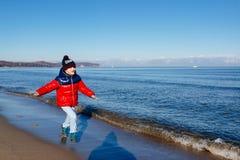 Gelukkig weinig kindjongen die op het strand lopen stock foto