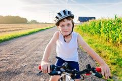 Gelukkig weinig kindjongen in witte helm op fiets stock afbeelding
