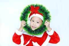 Gelukkig weinig kindmeisje in Kerstmankostuum met holdingskerstmis om kroon op haar gezicht op witte achtergrond Vrolijke Kerstmi royalty-vrije stock foto's
