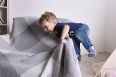 Gelukkig weinig leuk jongensspel op leunstoel in woonkamer stock foto