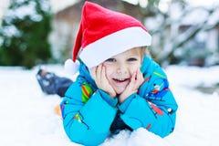 Gelukkig weinig peuterjongen die op de hoed van Kerstmissanta wachten Stock Fotografie