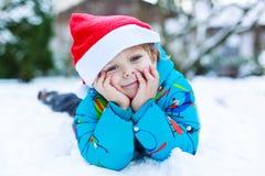 Gelukkig weinig peuterjongen die op de hoed van Kerstmissanta wachten Stock Foto's