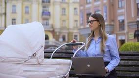 Gelukkig werkend mamma met laptop slingeren pasgeboren in vervoer, familie en carrière stock videobeelden