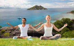 Gelukkig yoga doen en paar die in openlucht mediteren Stock Afbeelding