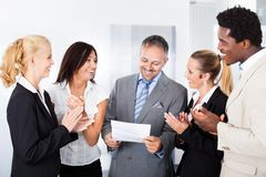 Gelukkig zakenlui die zakenman toejuichen Stock Afbeeldingen