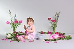 Gelukkig zit een klein kind met een bloem, grijze achtergrond Royalty-vrije Stock Foto's