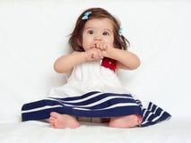 Gelukkig zit weinig kindmeisje op witte handdoek, gelukkige emotie en zeer verraste gezichtsuitdrukking, de vinger in mond Royalty-vrije Stock Fotografie