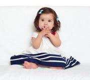 Gelukkig zit weinig kindmeisje op witte handdoek, gelukkige emotie en zeer verraste gezichtsuitdrukking, de vinger in mond Royalty-vrije Stock Afbeeldingen