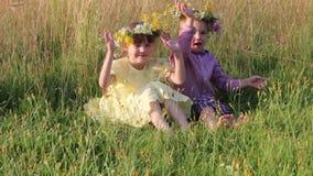 Gelukkig zitten weinig jongen en meisje in kronen in droog gras stock footage