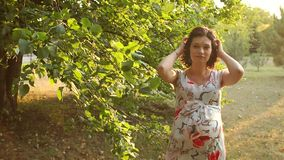 Gelukkig zwanger meisje die in het de zomerpark lopen stock footage