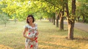 Gelukkig zwanger meisje in het Park bij zonsondergang Langzame mo stock video