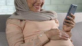 Gelukkig zwanger moslimvrouw het letten op beeldverhaal op smartphone en het glimlachen, app stock footage