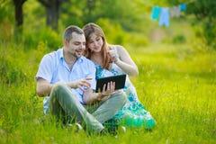 Gelukkig zwanger paar met tablet Royalty-vrije Stock Afbeeldingen