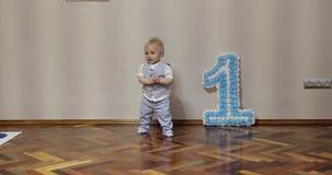 Gelukkige éénjarigenjongen het vieren verjaardag en het dansen op de vloer stock videobeelden
