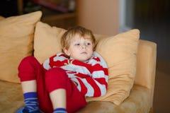 Gelukkige aanbiddelijke jong geitjejongen het letten op televisie terwijl het liggen Grappig gezond kind die van beeldverhalen ge stock foto
