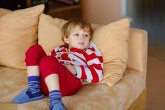 Gelukkige aanbiddelijke jong geitjejongen het letten op televisie terwijl het liggen Grappig gezond kind die van beeldverhalen ge royalty-vrije stock afbeelding
