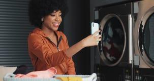 Gelukkige aantrekkelijke Afrikaanse Amerikaanse jonge vrouw die een videopraatje hebben bij laundromat Zelfbedienings openbare wa stock videobeelden