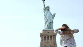 Gelukkige aantrekkelijke glimlachende Europese toeristenvrouw die op de telefoon bij Standbeeld van Vrijheid in New York op een z stock video