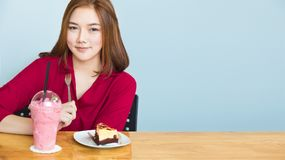 Gelukkige aantrekkelijke jonge Aziatische vrouw die bij een lijst situeren die glimlachen bij Royalty-vrije Stock Foto