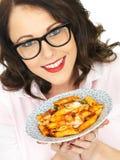 Gelukkige Aantrekkelijke Jonge Spaanse Vrouw die een Plaat van Tomaat en Basil Penne Pasta houden Royalty-vrije Stock Fotografie