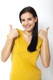 Gelukkige aantrekkelijke jonge vrouw die duimen tonen, o.k. Stock Afbeelding