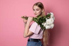 Gelukkige aantrekkelijke jonge vrouw met blondehaar die roze t-shirt dragen die wit bloemenboeket houden stock foto