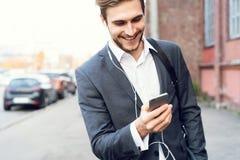Gelukkige aantrekkelijke jonge zakenman die en mobiele telefoon in openlucht lopen met behulp van stock afbeeldingen
