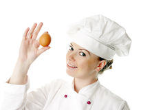 Gelukkige aantrekkelijke kokvrouw met ei Stock Afbeeldingen