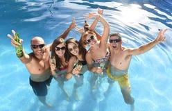 Gelukkige aantrekkelijke mannen en vrouwen in bikini die bad hebben bij het zwembad van de hoteltoevlucht het drinken bier stock afbeelding