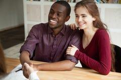 Gelukkige aantrekkelijke multiraciale paar het schudden handen met adviseur o stock afbeelding