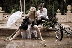 Gelukkige aantrekkelijke paarzitting bij rand van fontein met uitstekende fiets en rozen stock foto's