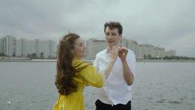 Gelukkige aantrekkelijke vrouw die met haar vriend bij de dijk in de stad dansen stock video