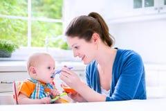 Gelukkige aby jongen die zijn eerste stevig voedsel eten witn zijn moeder stock foto's
