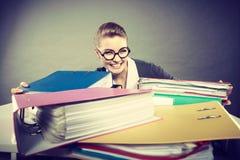 Gelukkige accountant met stapels van bindmiddelen Stock Afbeeldingen
