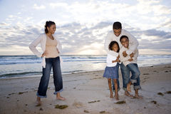 Gelukkige Afrikaans-Amerikaanse familie van vier op strand Royalty-vrije Stock Foto