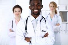Gelukkige Afrikaanse Amerikaanse arts met medisch personeel bij het ziekenhuis Multi etnische mensengroep stock fotografie